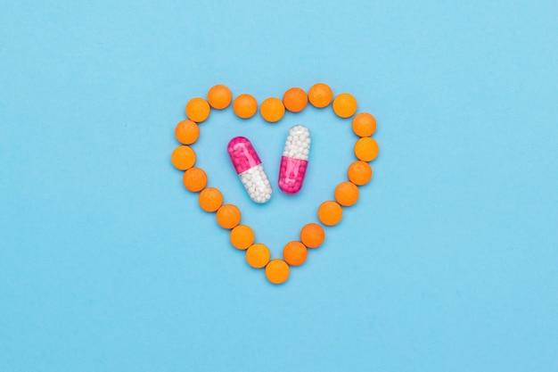 Um coração feito de comprimidos com duas cápsulas medicinais dentro