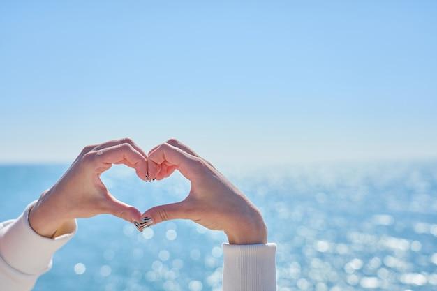 Um coração feito de mãos de uma mulher contra um mar turvo como um bokeh