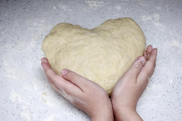 Um coração feito de massa é segurado pelas mãos das crianças.