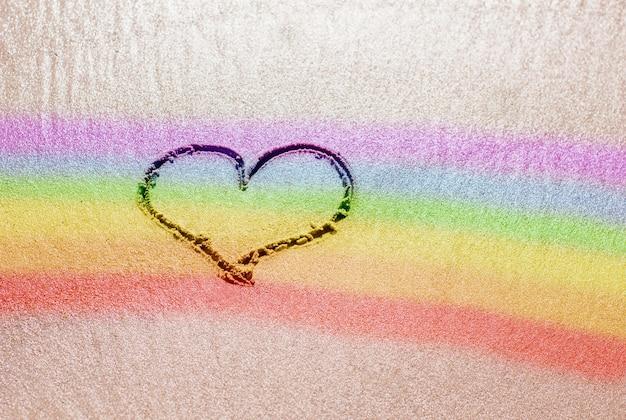Um coração pintado na areia com um símbolo lgbt é uma bandeira multicolorida do arco-íris, um símbolo de igualdade e liberdade de gênero