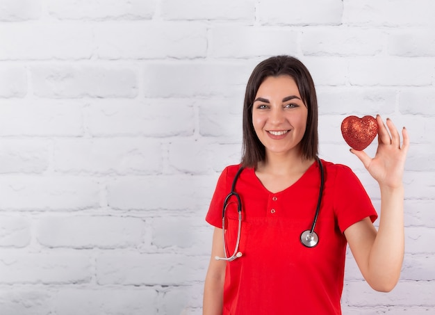 Um coração vermelho brilhante nas mãos de um médico