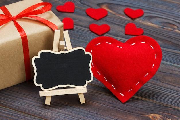 Um coração vermelho com placa preta e corações pequenas.