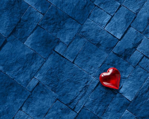 Um coração vermelho contra uma pedra azul sólida.