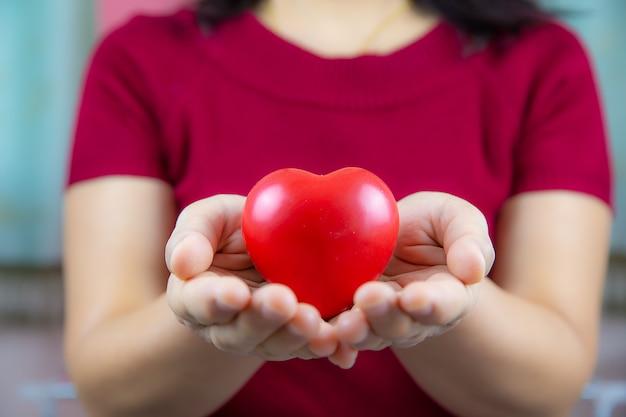 Um coração vermelho em forma de balão na mão da mulher para o conceito do dia de amor e felicidade, dia dos namorados, 14 de fevereiro.