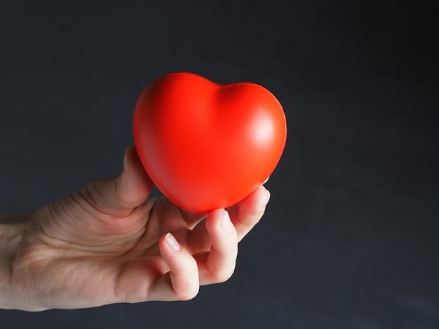 Um coração vermelho na mão de uma mulher em um fundo escuro