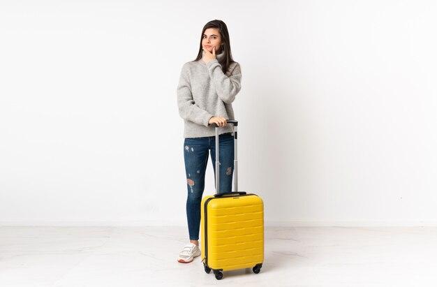 Um corpo inteiro de uma mulher viajante com uma mala isolada parede branca pensando uma idéia