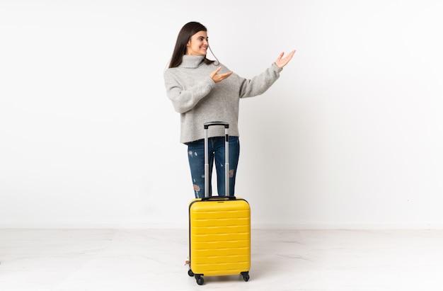Um corpo inteiro de uma mulher viajante com uma mala sobre parede branca estendendo as mãos para o lado para convidar para vir