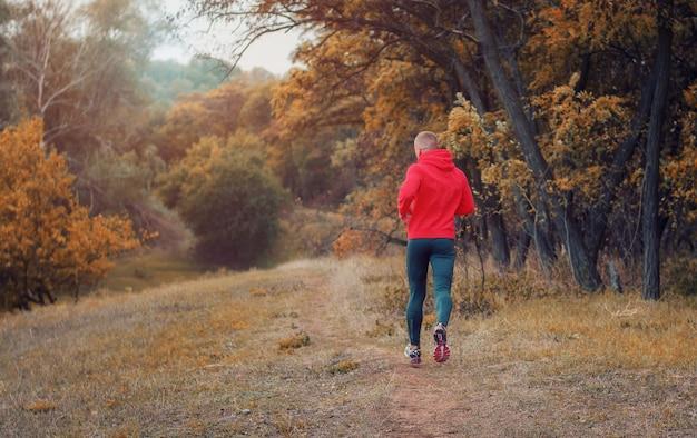 Um corredor atlético magro em uma leggins preta e jaqueta vermelha corre no colorido colina amarela floresta outonal.