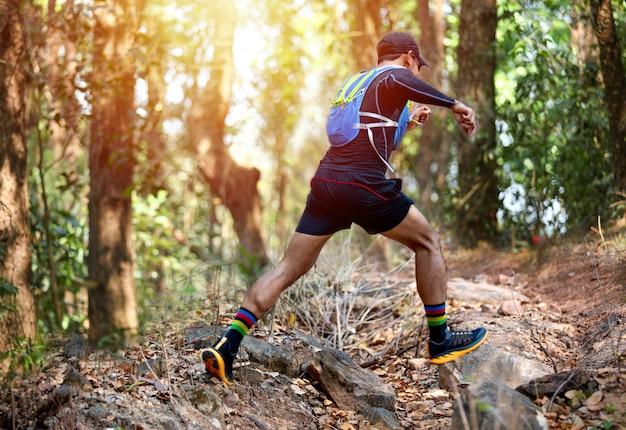Um corredor de homem usando sapatos esportivos para trilha correndo na floresta