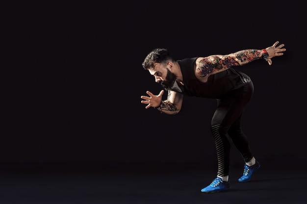 Um corredor de velocista jovem homem caucasiano correndo no estúdio de silhueta em fundo escuro.