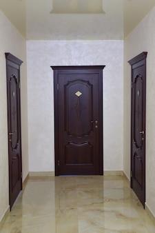 Um corredor em um hotel ou prédio de escritórios com vista em perspectiva. três portas marrons fechadas no final e nas laterais