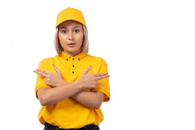 Um correio fêmea da vista dianteira na camisa amarela do tampão amarelo e nas calças de brim pretas que levantam no serviço branco da menina da entrega do fundo
