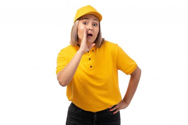 Um correio feminino de vista frontal na camisa amarela, boné amarelo e calça jeans preta posando sussurrando em branco