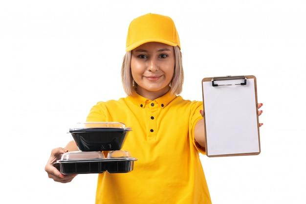 Um correio feminino de vista frontal na camisa amarela, boné amarelo e calça jeans preta segurando tigelas com comida e o bloco de notas sorrindo em branco