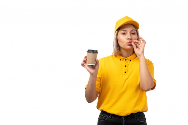Um correio feminino de vista frontal na camisa amarela de boné amarelo e calça jeans preta, segurando a xícara de café no fundo branco