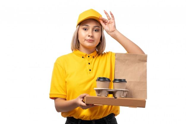 Um correio feminino de vista frontal no boné amarelo de camisa amarela segurando pacotes de café e comida em branco