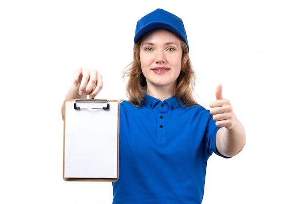 Um correio feminino jovem vista frontal na camisa azul boné azul sorrindo mostrando como sinal e segurando o bloco de notas em branco