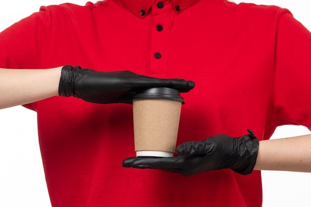 Um correio feminino vista frontal em luvas de camisa vermelha preta e segurando a xícara de café
