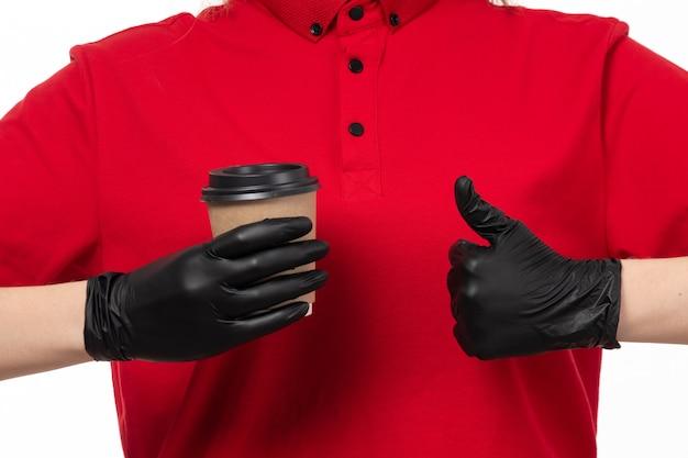 Um correio feminino vista frontal na camisa vermelha e luvas pretas, mostrando como sinal segurando a xícara de café