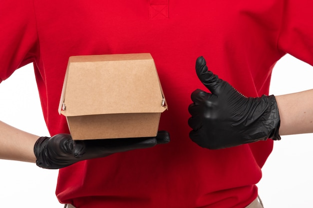 Um correio feminino vista frontal na camisa vermelha e luvas pretas, segurando o pacote com comida