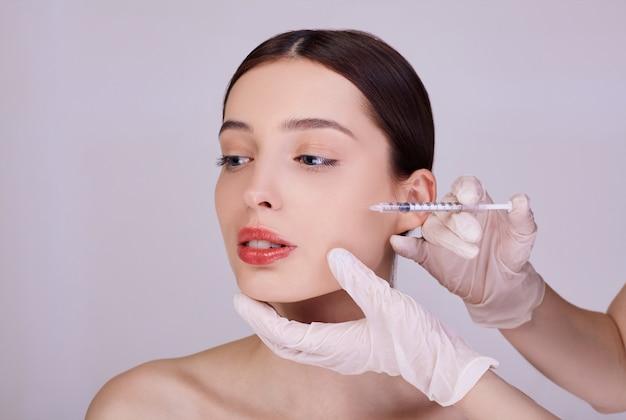Um cosmetologista faz procedimentos antienvelhecimento para rosto de mulher.