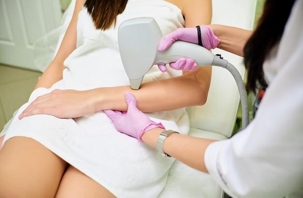 Um cosmetologista realiza um procedimento para depilação a laser do corpo de uma menina