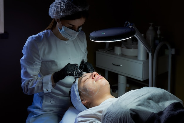 Um cosmetologista vestindo uma máscara facial e luvas médicas descartáveis esfrega o creme no rosto de uma mulher para tonificar sua pele