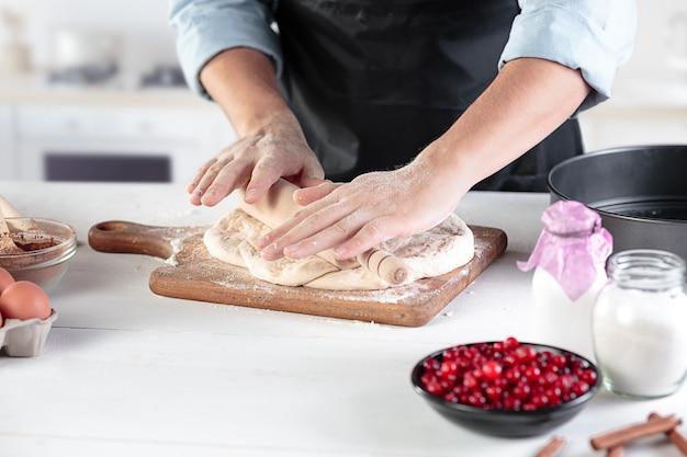 Um cozinheiro com ovos em uma cozinha rústica contra a parede das mãos dos homens