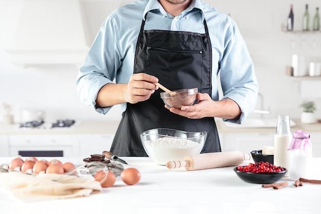Um cozinheiro com ovos em uma cozinha rústica contra as mãos dos homens