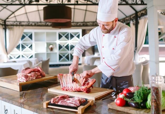 Um cozinheiro de homem corta carne com uma faca em um restaurante.