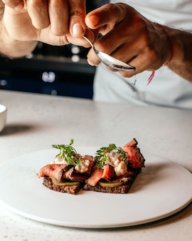 Um cozinheiro de vista frontal preparando uma refeição projetando uma refeição dentro de um prato de carne frita