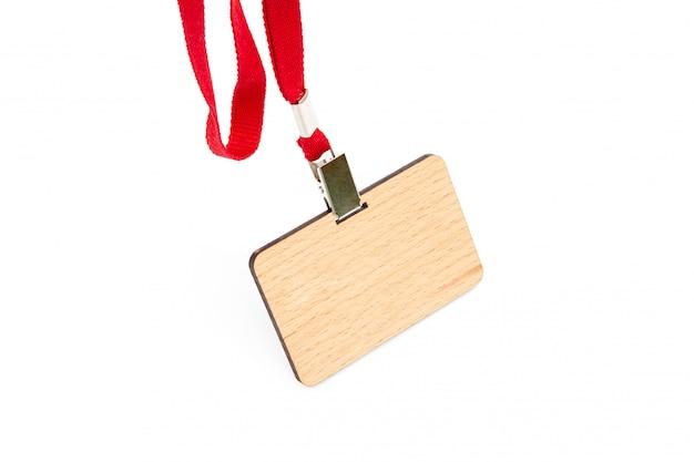 Um crachá de madeira com um campo vazio sob o nome do empregado paira sobre um laço vermelho. isolado