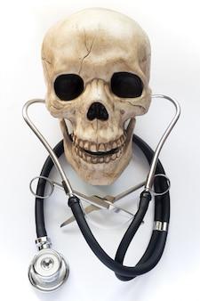 Um crânio esqueleto com tesoura médica e estetoscópio