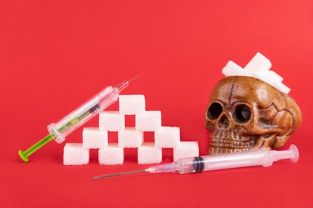 Um crânio humano cheio de cubos de açúcar branco refinado em um fundo vermelho. copie o espaço.