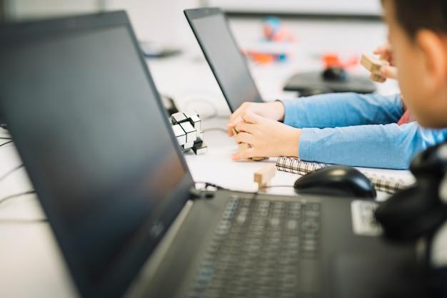 Um, criança menina, tocando, com, cubo madeira, quebra-cabeça, com, laptop, branco, escrivaninha