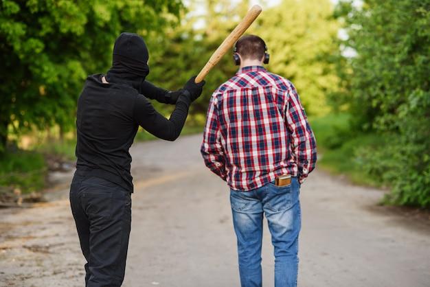 Um criminoso em roupas pretas com um taco de beisebol nas mãos ataca um homem. furtos na rua durante o dia.
