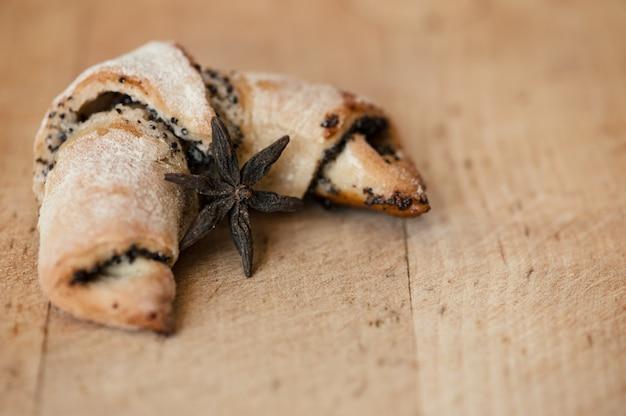 Um croissant com sementes de papoila em uma superfície de madeira e um anis estrelado