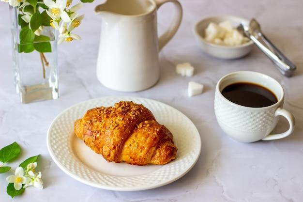 Um croissant e café em uma superfície de mármore