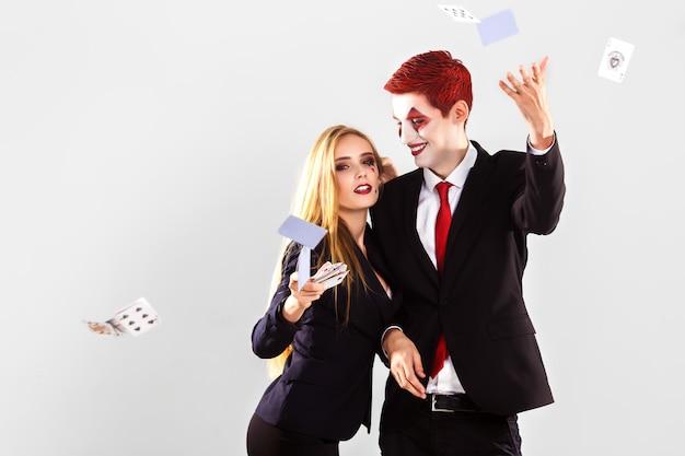 Um crupiê de moça bonita e um garoto com um coringa de maquiagem artística. conceito de jogo e cassino. foto de estúdio. fundo branco .