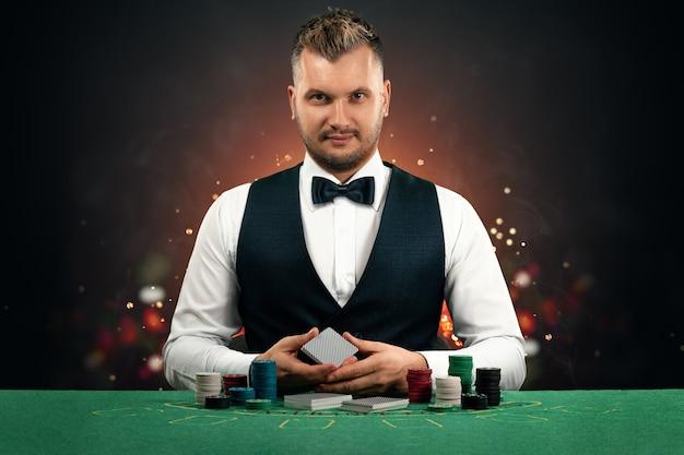 Um crupiê está sentado a uma mesa com fichas e cartas de jogar