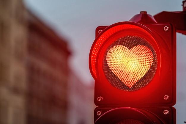 Um cruzamento da cidade com um semáforo, semáforo com formato de coração vermelho no semáforo