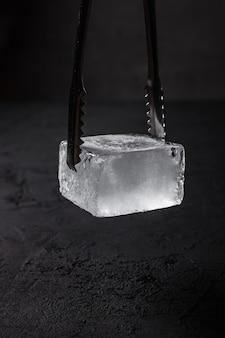 Um cubo de gelo congelado para copo cupê em pinças de gelo de barman, fundo escuro