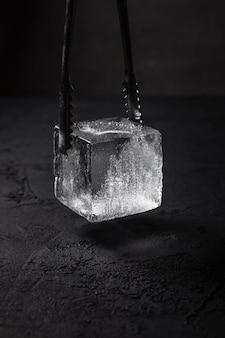 Um cubo de gelo quadrado transparente para copo de pedras em pinças de gelo de barman, fundo escuro