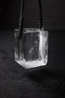 Um cubo de gelo transparente para copo de pedras em pinças de gelo de barman, fundo escuro