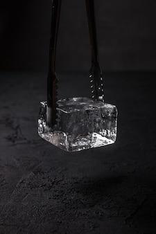 Um cubo de gelo transparente para um copo coupé em pinças de gelo de barman, fundo escuro
