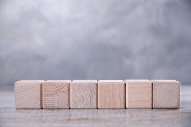 Um cubo de madeira em branco em cima da mesa.