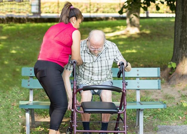 Um cuidador espanhol está ajudando a se sentar em um banco no parque, um homem idoso
