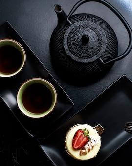 Um cupcake com creme e morango, chaleira preta e duas xícaras de chá.