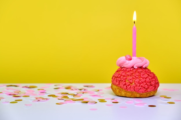 Um cupcake de aniversário colorido com uma vela e confetes em um fundo amarelo