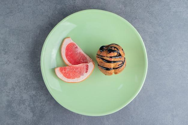Um cupcake de chocolate com rodelas de toranja